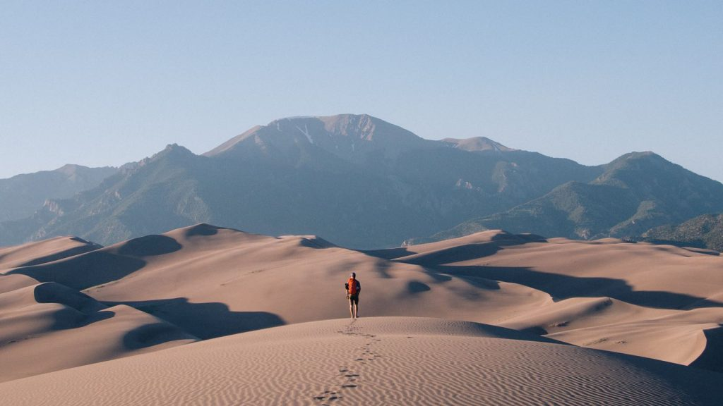 A man walking in the desert, leaving footprints behind him in the sand